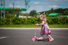 Little girl in dress riding her scooter on the park. Stock Photo