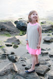 Little girl in dress on the rocks in the sea looking up Royalty Free Stock Image