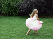 Little girl in dress running Stock Images