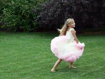 Little girl in dress running Stock Images
