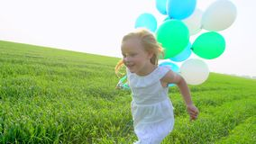 Little girl in a dress running through green wheat field with balloons in hand. Child, kid running in garden and