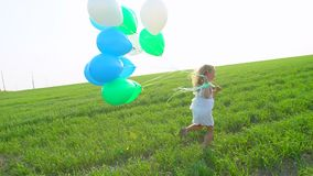 Little girl in a dress running through green wheat field with balloons in hand. Child, kid running in garden and stock video footage