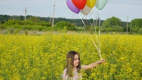 Little girl in a dress running through yellow wheat field with balloons in hand.  Royalty Free Stock Photos
