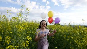 Little girl in a dress running through yellow wheat field with balloons in hand.  Stock Photo