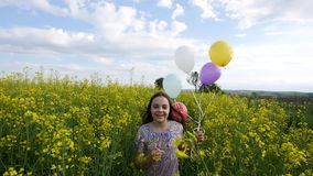 Little girl in a dress running through yellow wheat field with balloons in hand.  Stock Images