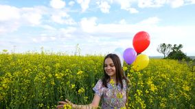 Little girl in a dress running through yellow wheat field with balloons in hand. slow motions.  Stock Photo