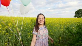 Little girl in a dress running through yellow wheat field with balloons in hand. slow motions.  Stock Photography