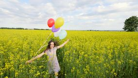 Little girl in a dress running through yellow wheat field with balloons in hand. slow motions.  Royalty Free Stock Images