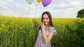 Little girl in a dress running through yellow wheat field with balloons in hand. slow motions.  Stock Image