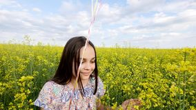 Little girl in a dress running through yellow wheat field with balloons in hand. slow motions.  Stock Images