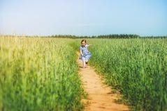 Little girl in a dress runs across the field on a sunny day. Little cute girl in a dress runs across the field on a sunny day royalty free stock photo
