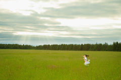 Little girl in dress runs on meadow Stock Images