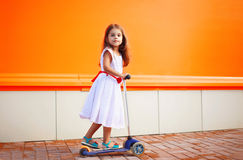 Little girl in dress on the scooter Stock Images