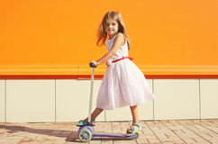 Little girl in dress on the scooter against the colorful wall Royalty Free Stock Photo