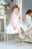 Little girl in dress sitting in front of mirror Stock Photography