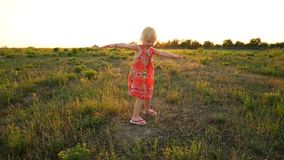 A little girl dress is spinning in the rays of the setting sun. stock footage
