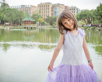 Little girl in dress standing in front of a lake Stock Photos