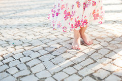 Little girl in dress stands on stone pavement. Close-up Stock Photos