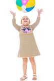 Little girl in dress throws up the ball. Isolated on white background Royalty Free Stock Photography
