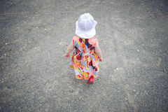 Little girl in dress and white hat walking Stock Photography