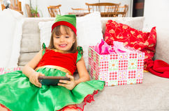 Little girl dressed as Christmas elf holding Stock Photos