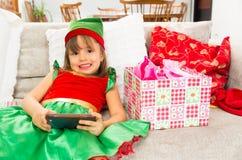 Little girl dressed as Christmas elf holding Stock Image