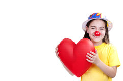 Little girl dressed as a clown. With a heart in the hands Stock Photo
