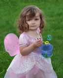Little girl dressed as fairy with bubble wand. Young girl child playing with bubbles dressed in a pink princess dress with fairy wings royalty free stock images