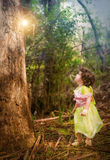 Little girl dressed as a fairy standing in forest Stock Images