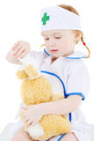 Little girl dressed as nurse bandages head to toy rabbit Royalty Free Stock Images