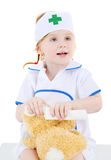 Little girl dressed as nurse bandages head to toy rabbit Stock Photos