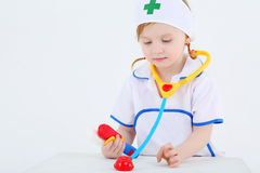 Little girl dressed as nurse plays with toy phonendoscope Royalty Free Stock Photos