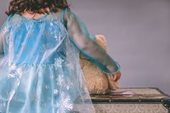 One little girl dressed as a princess holds a teddy bear while sitting on a chest. A little girl dressed as a princess holds a teddy bear while sitting on a Royalty Free Stock Photos