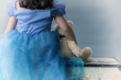 A little girl dressed as a princess holds a teddy bear while sitting on a chest. And facing a grey seamless background Royalty Free Stock Photos