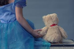 A little girl dressed as a princess holds a teddy bear while sitting on a chest. And facing a grey seamless background Royalty Free Stock Photography