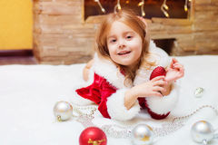 Little girl dressed as Santa with Christmas balls at home Royalty Free Stock Images