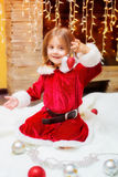 Little girl dressed as Santa with Christmas balls at home Stock Photo