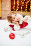 Little girl dressed as Santa with Christmas balls at home Royalty Free Stock Photos