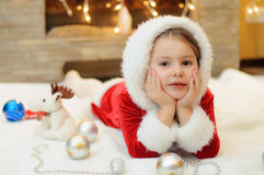 Little girl dressed as Santa by the fireplace Stock Photos
