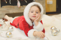 Little girl dressed as Santa by the fireplace Royalty Free Stock Images