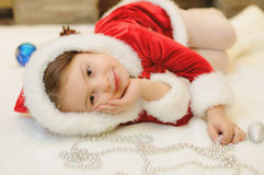 Little girl dressed as Santa by the fireplace Stock Photography
