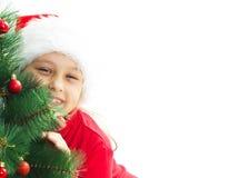 Little girl dressed as Santa hugging Stock Photo