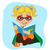 Little girl dressed as a superhero reading a comic book Royalty Free Stock Photos