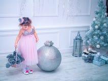 Little girl dressed in beautiful fashion white flower dress posing near Christmas tree Royalty Free Stock Photos