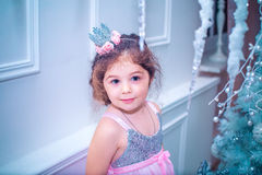 Little girl dressed in beautiful fashion white flower dress posing near Christmas tree Stock Image