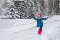 Little girl dressed in a blue coat and a pink hat and boots, hamming and playing in the winter forest Royalty Free Stock Images