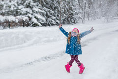 Little girl dressed in a blue coat and a pink hat and boots, hamming and playing in the winter forest Stock Photo