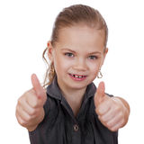 Little girl dressed in blue is showing thumb up gesture using bo Royalty Free Stock Photography