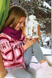Little girl dressed in a cozy sweater sits on a windowsill on Ch Stock Image
