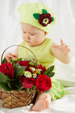 Little girl dressed in greenish clothes and hat sitting on bedding Royalty Free Stock Photography